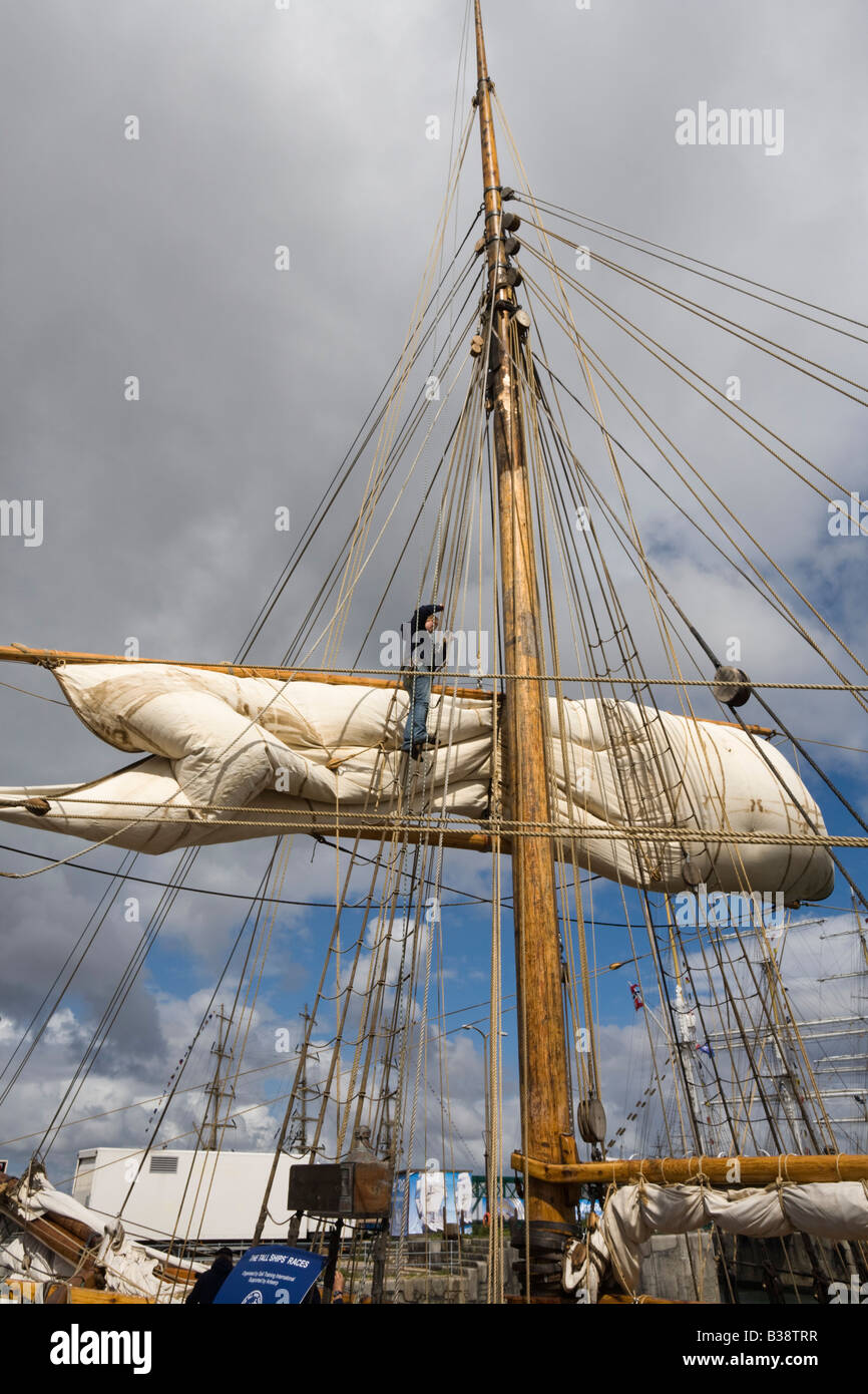 Person sorting ropes and sail high up on square rigged mast on boat in Tall Ships race sailor working Stock Photo
