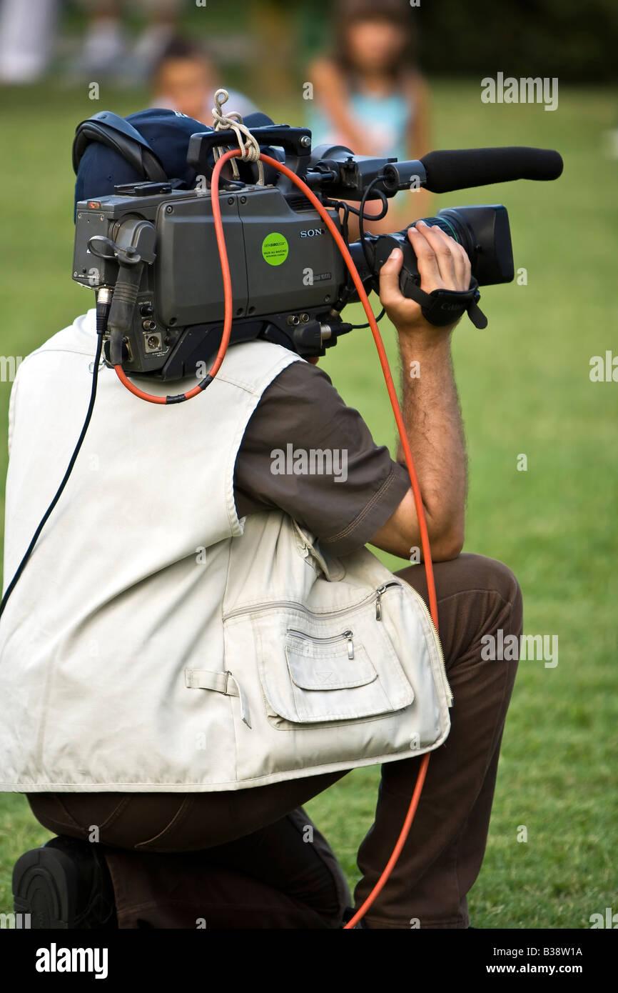 Professional TV news cameraman. - Stock Image