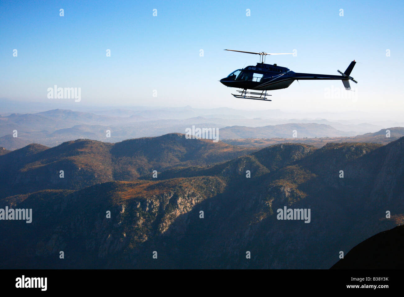 Aerial view of a helicopter flying in a scenic mountainous area - Stock Image