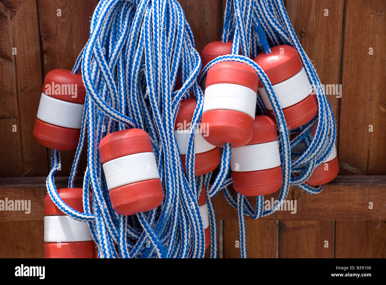 Swimming pool lane floats hang on a fence as their summer storage location - Stock Image