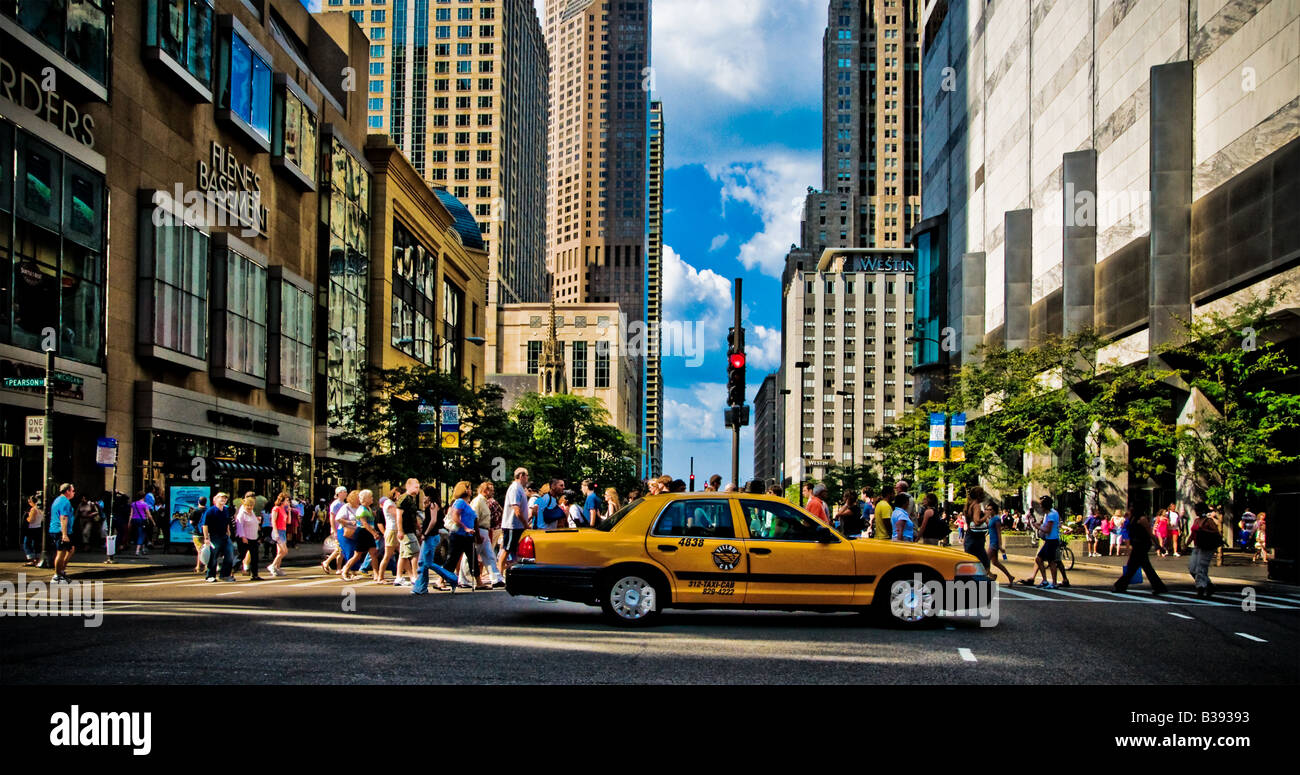 A parade of people walk across an intersection in Chicago while a taxi cab waits for them to clear. - Stock Image