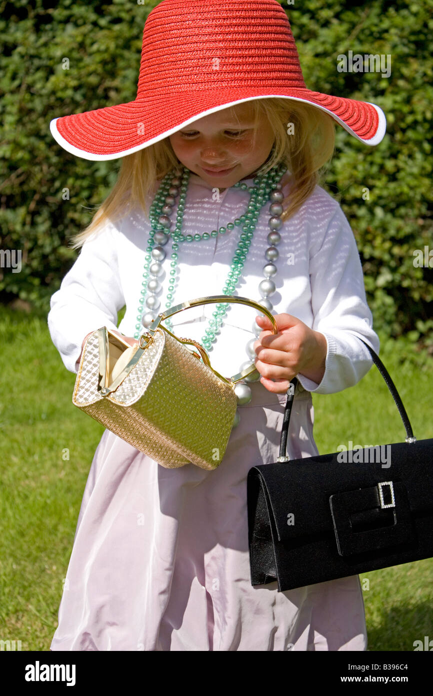 Three year old girl dressing up in grown up clothing outside in garden UK - Stock Image