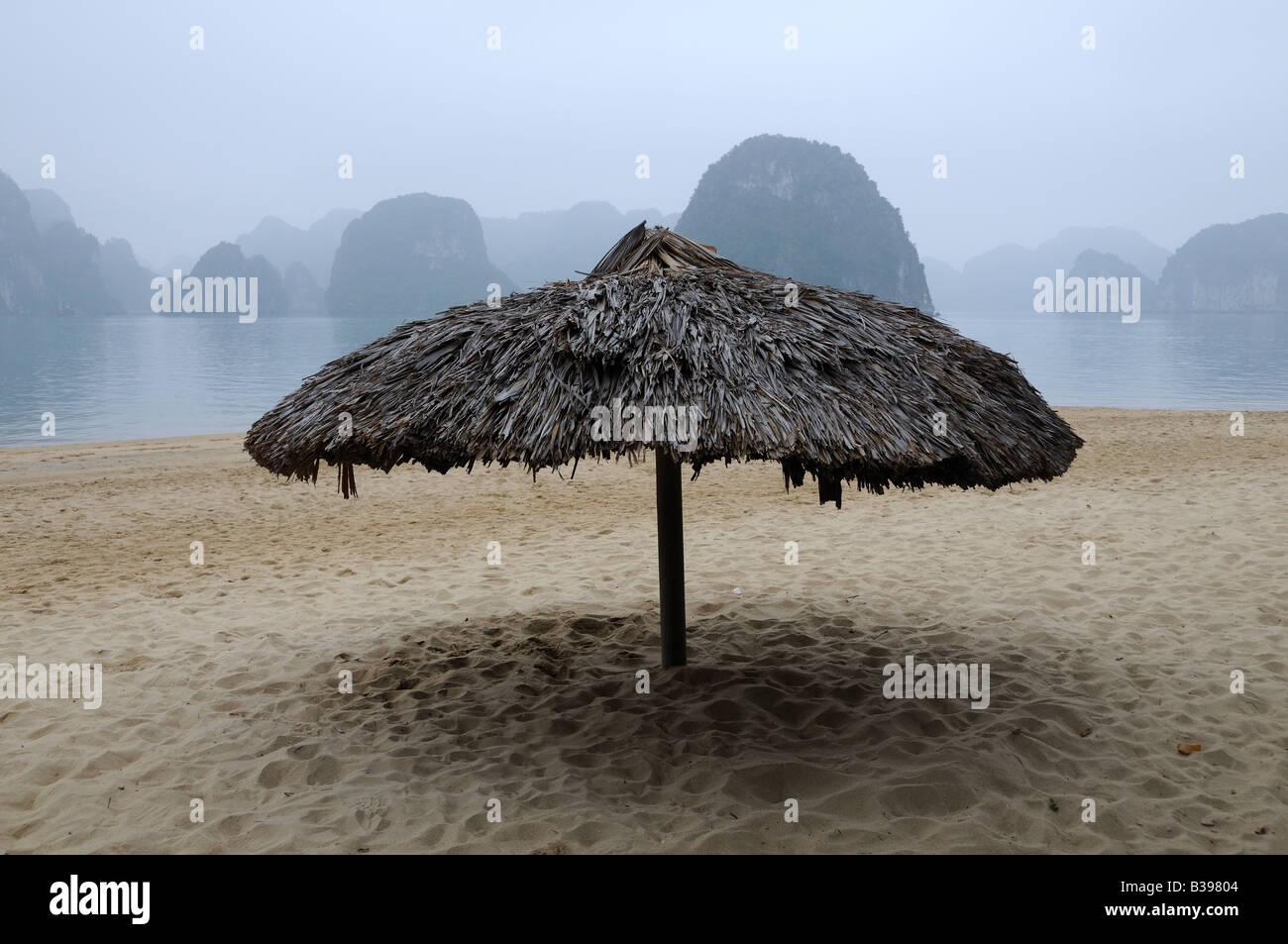 Straw umbrella on a beach misty morning Halong Bay Vietnam - Stock Image