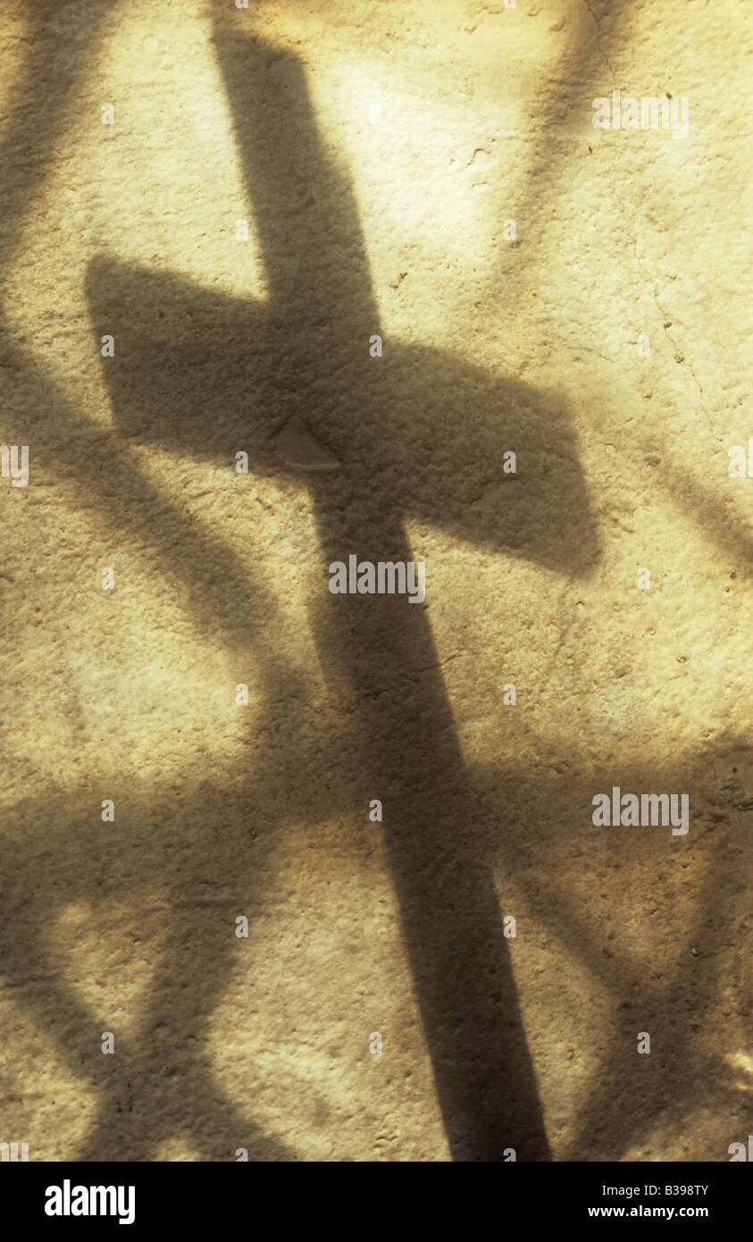 Shadow of crucifix cast onto cream painted rough wall with projection of plain diamond leaded panes of church windows - Stock Image
