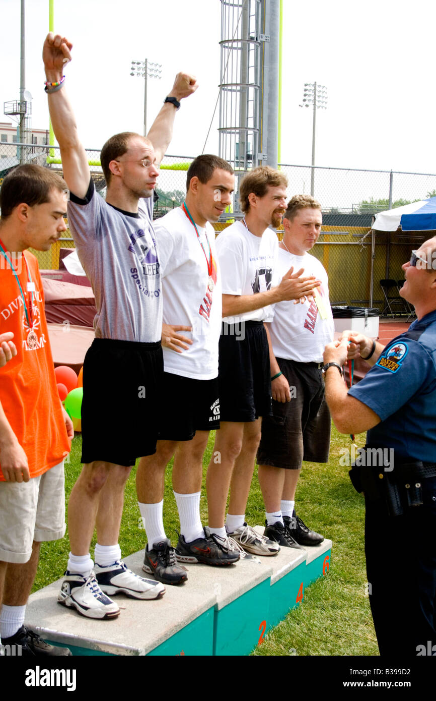 Policeman presenting 1st place medal to exuberant athlete. Special Olympics U of M Bierman Field. Minneapolis Minnesota - Stock Image