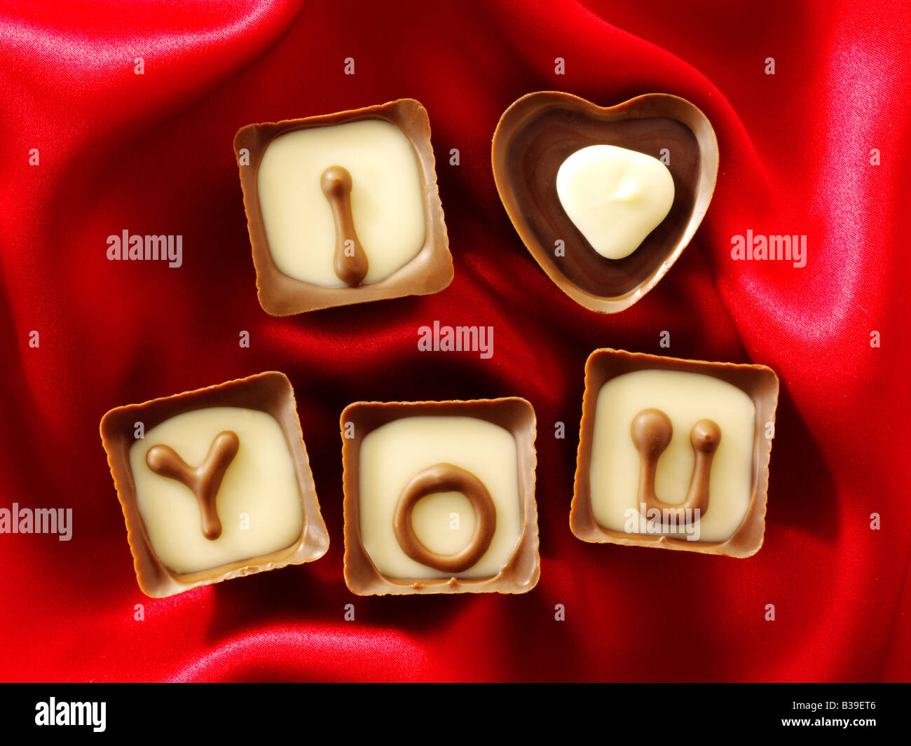 I Love You written in chocolates with red heart shaped chocolates. - Stock Image