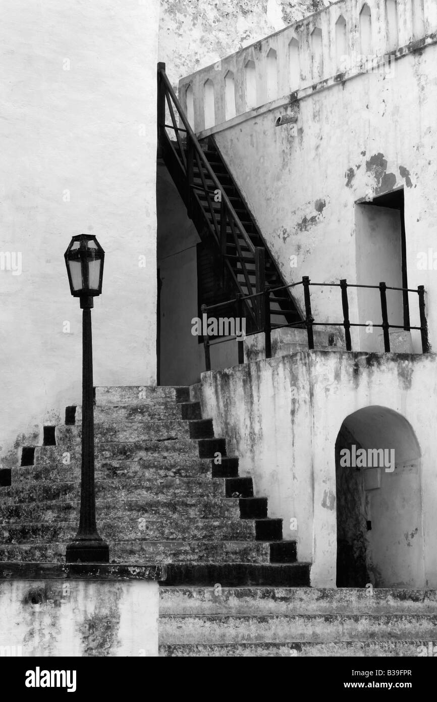 Castle stairs, lamp stand and arch lead up to a slave trade castle in Ghana, Africa - Stock Image