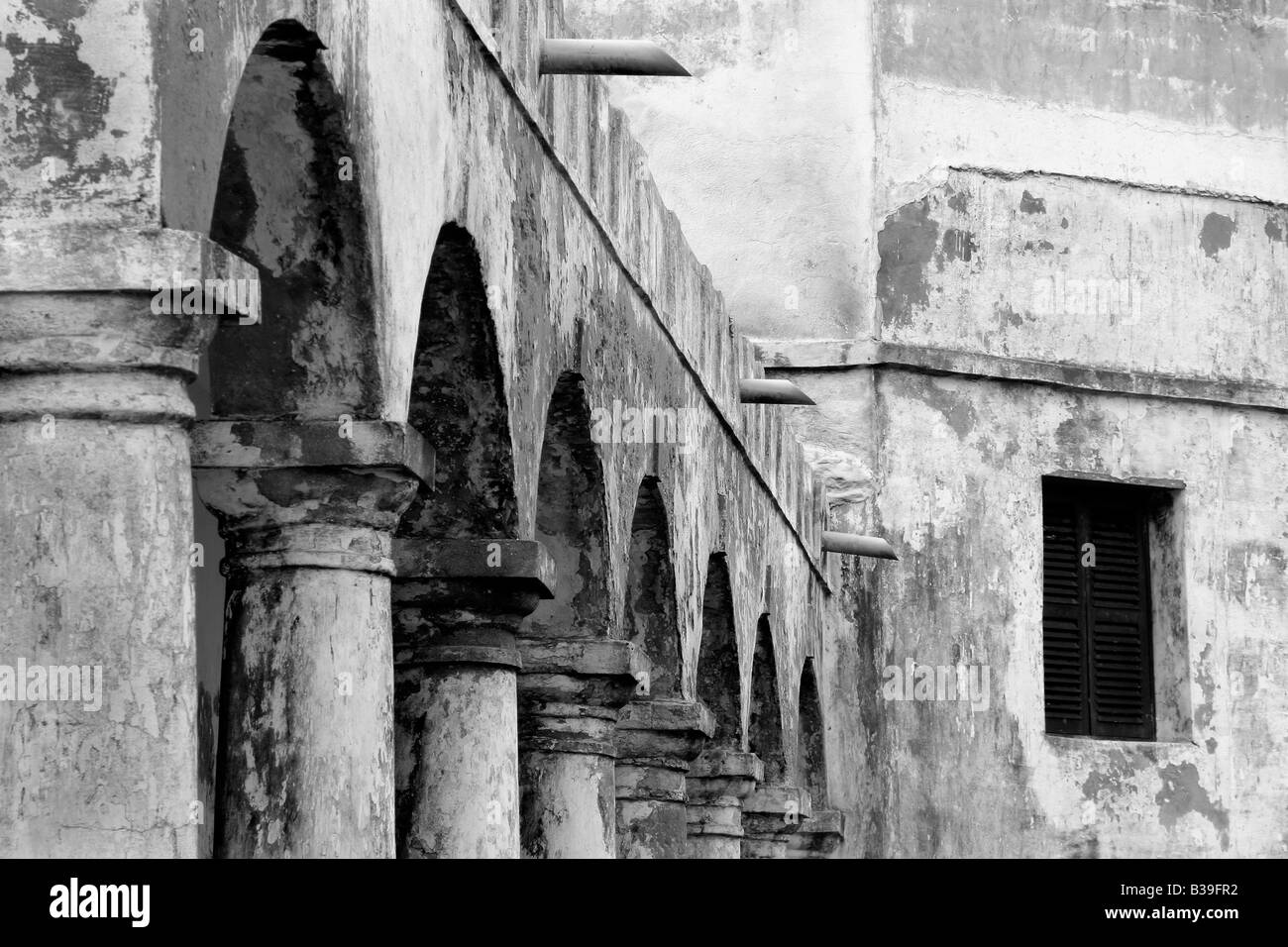 Pillars and arches lead to castle window in Ghana, Africa - Stock Image