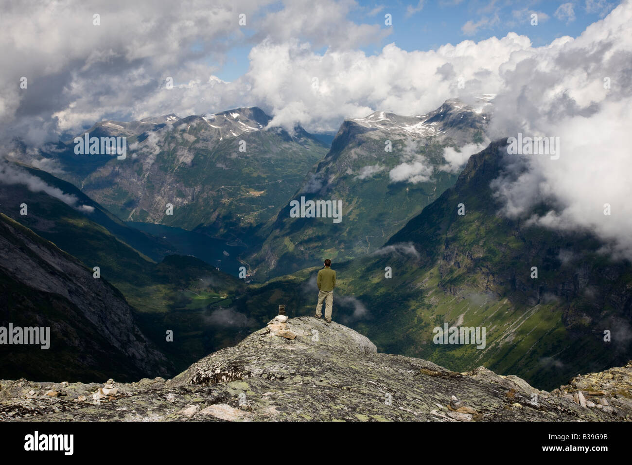Aerial perspective 1 young adult man 20's looking out at  Geiranger Fjord, Norway from Dalsnibba mountain plateau, dramatic blue sky, fluffy clouds Stock Photo