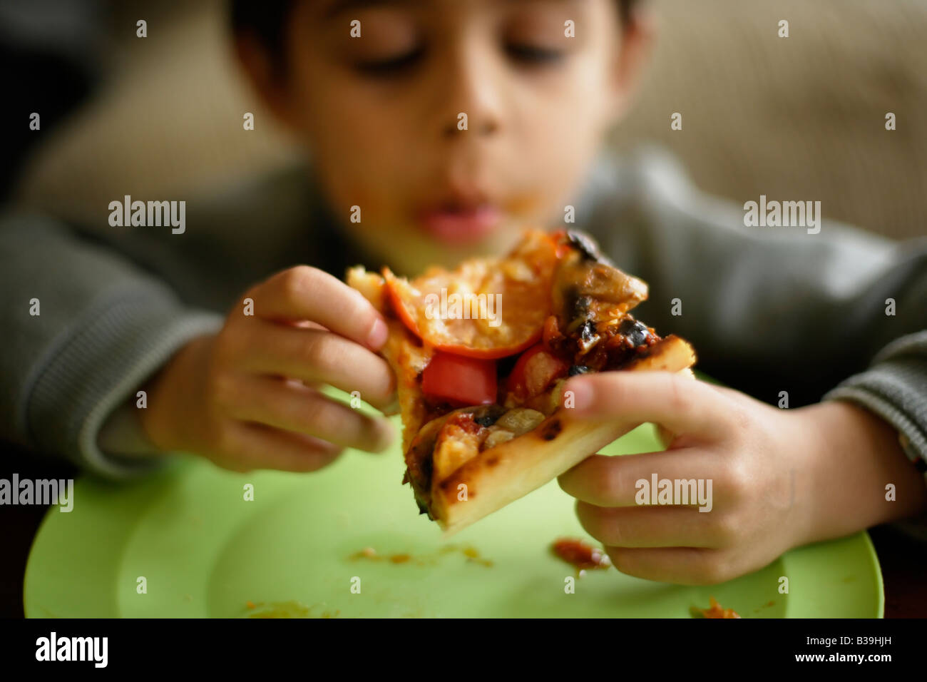 Homemade Pizza Six year old boy tucks into a slice of his mother s home cooking Mixed race Indian ethnic - Stock Image
