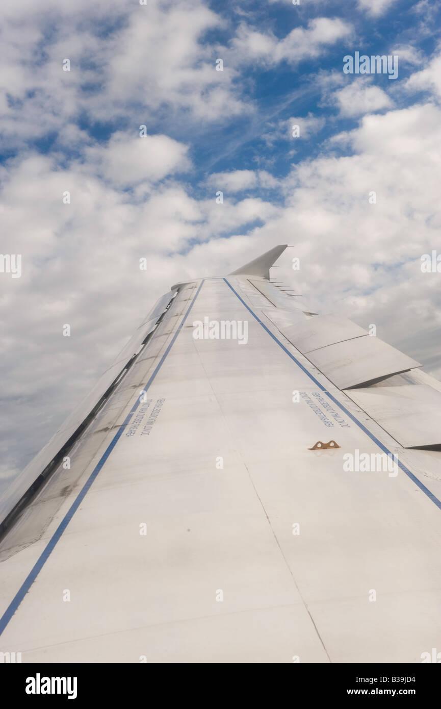 Passenger jet wing set against sky Stock Photo