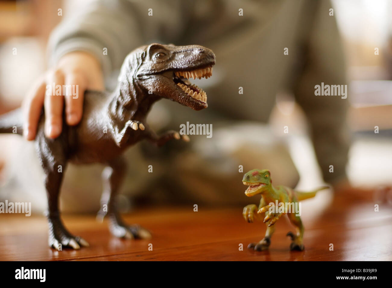 Model Tyrannosaurus rex in hands of six year old boy eating another toy dinosaur a Velociraptor - Stock Image