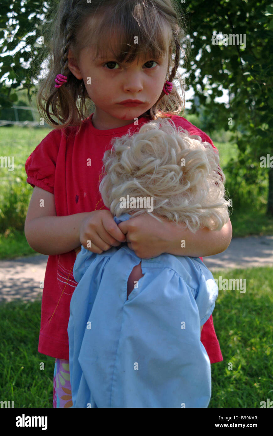 Little girl holding a doll looking unhappy - Stock Image