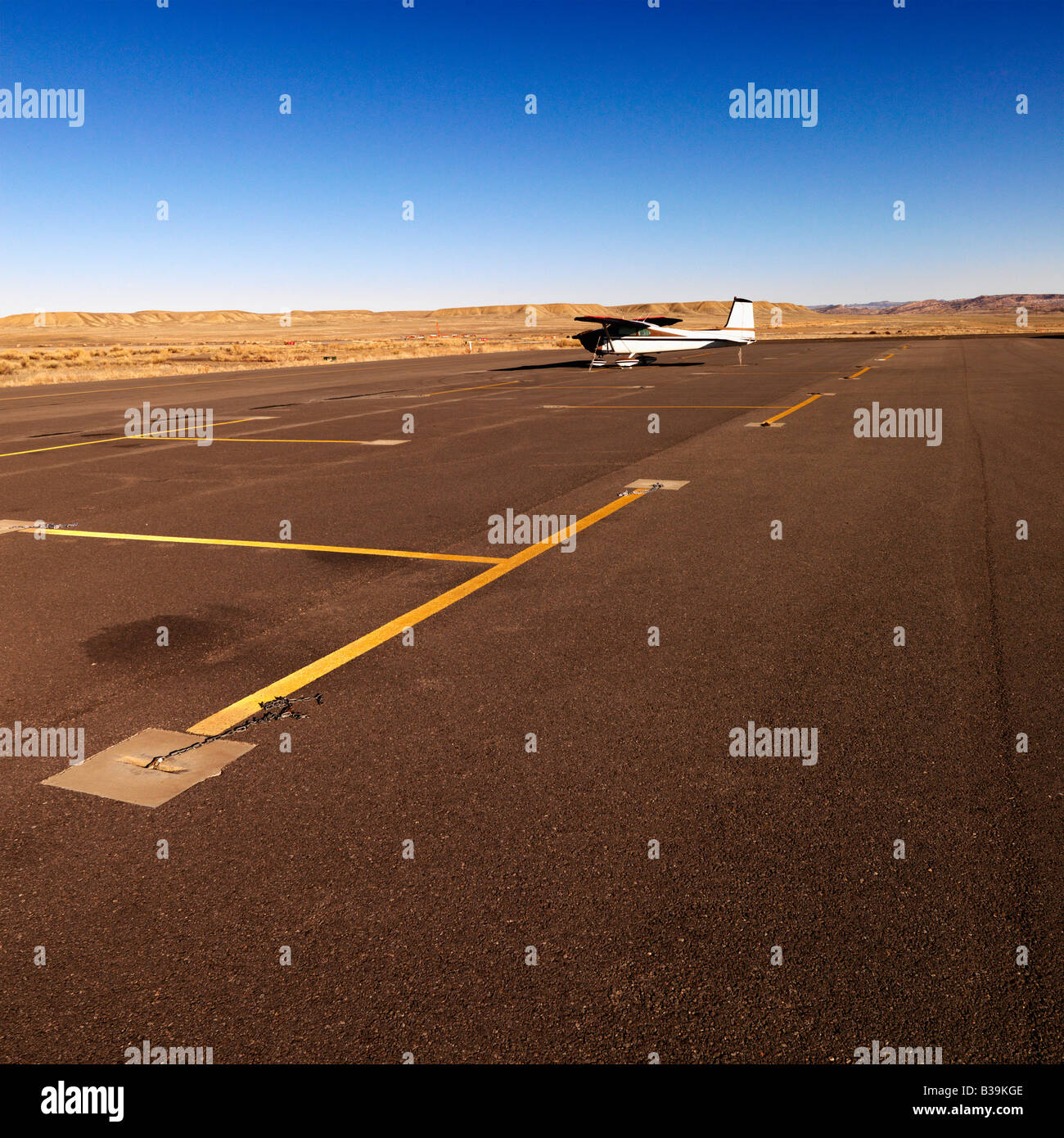 Plane in distance parked on tarmac at Canyonlands Field Airport Utah United States - Stock Image