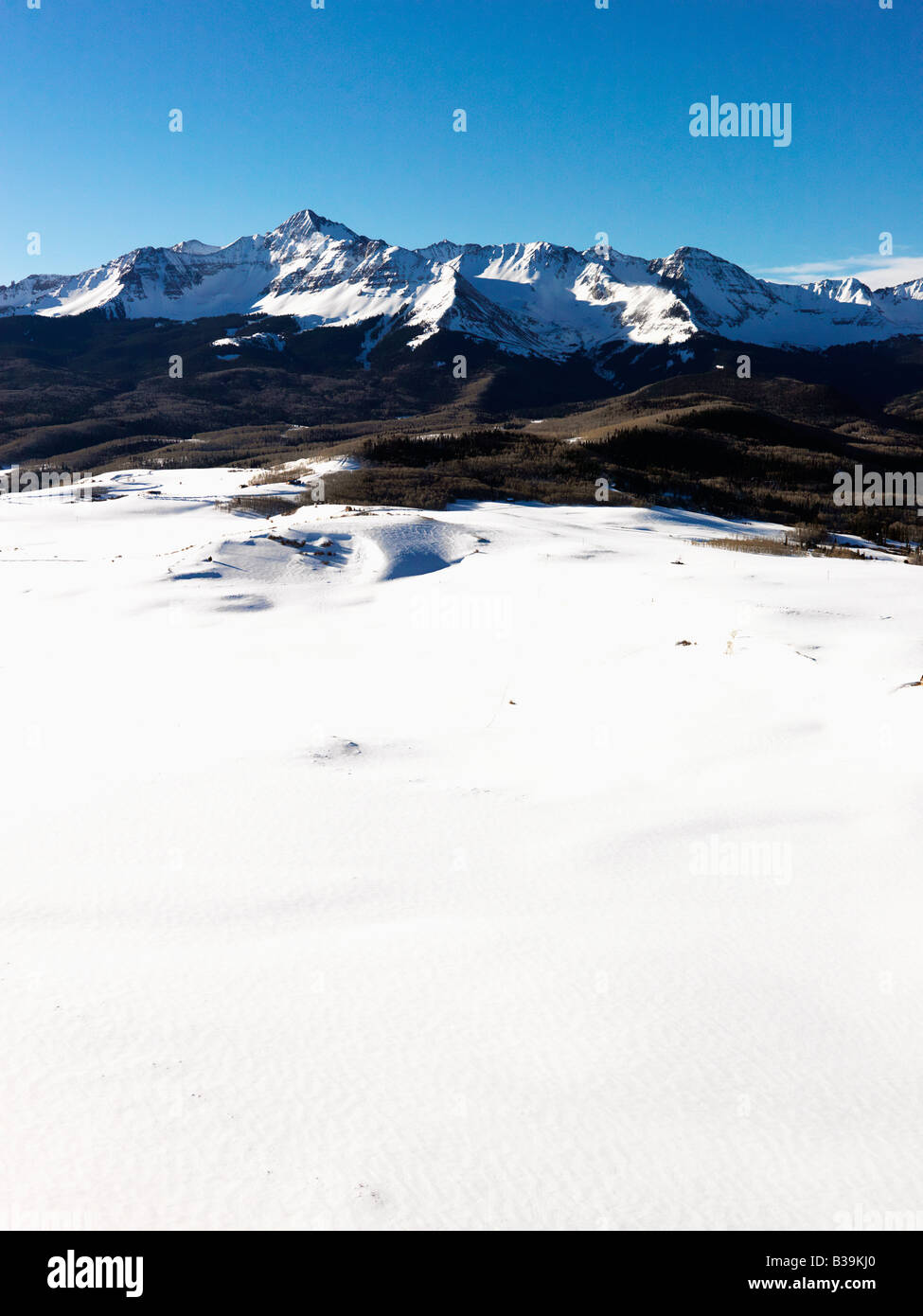 Aerial landscape of Colorado Rockies with snow covered valley in foreground - Stock Image