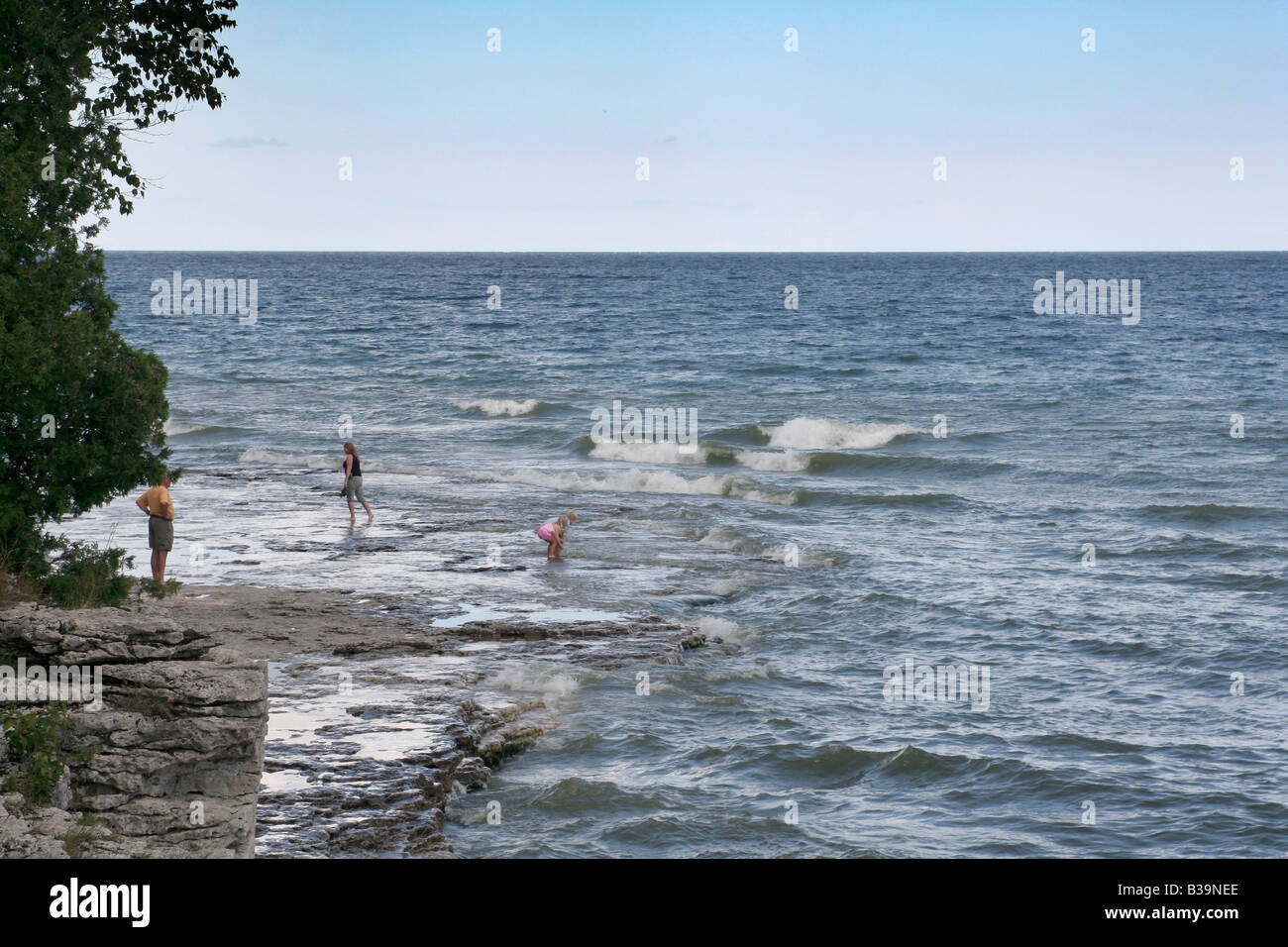 Family wading along rocky shore of Lake Michigan Door County Wisconsin & Family wading along rocky shore of Lake Michigan Door County Stock ...