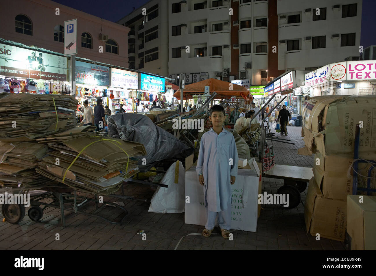 arab boy proudly posing in front of his wheelbarrow full of old cardboard boxes in the souk stolzer arabischer Junge Stock Photo