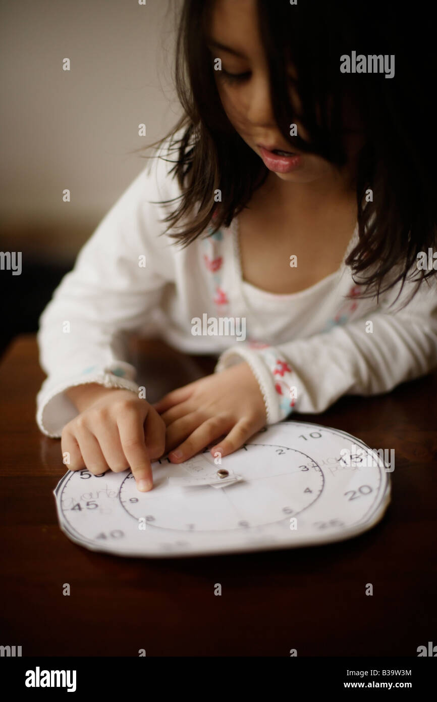 Five year old girl tells the time with a paper clock her older brother made at school - Stock Image