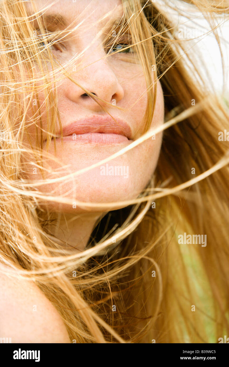 Close up portrait of attractive redheaded woman with windblown hair - Stock Image