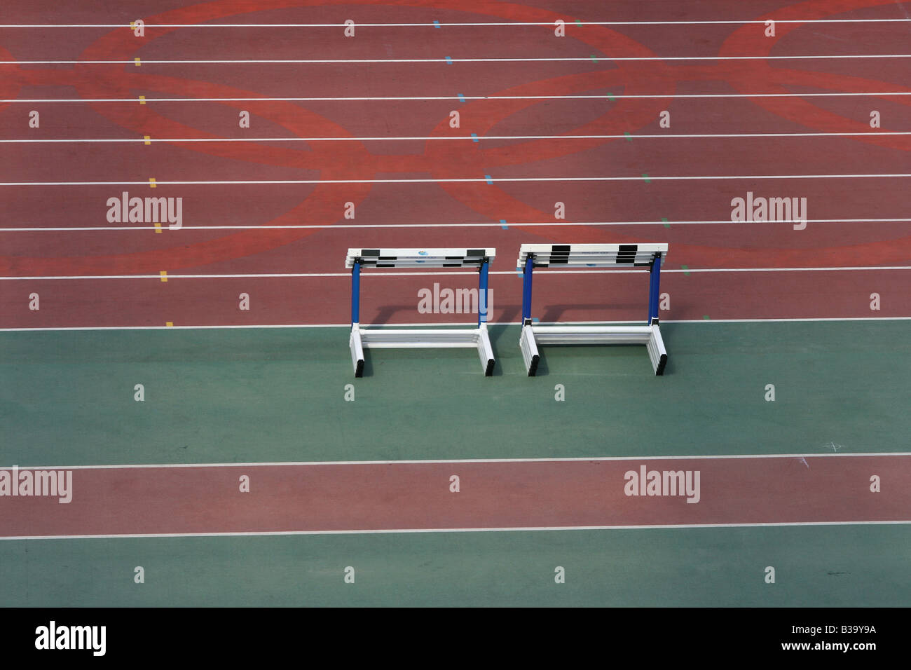 detail from empty athletics race track and stack of hurdles - Stock Image