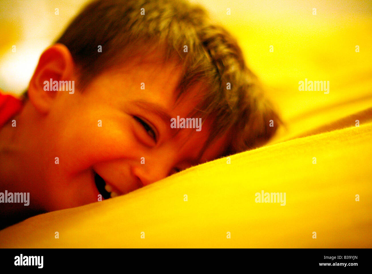 Child boy children baby kid pillow happy healthy play playing boyish grin smile smirk one two three four young giggle - Stock Image