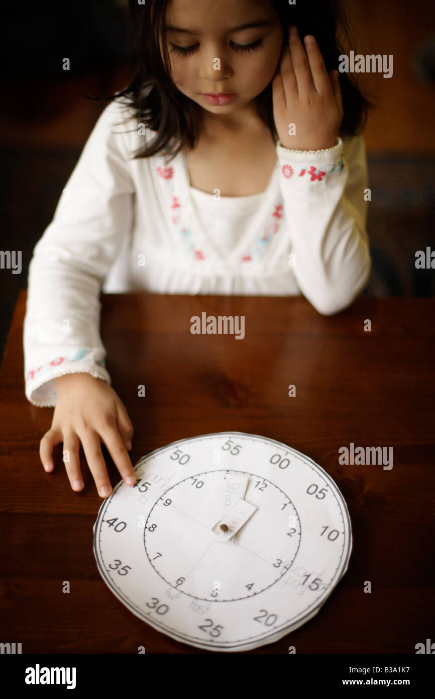 Five year old girl tells the time with a paper clock her older brother made at school Stock Photo