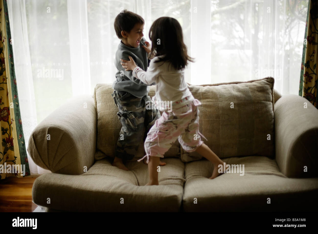 Brother aged six and sister five wrestle on sofa beside window - Stock Image