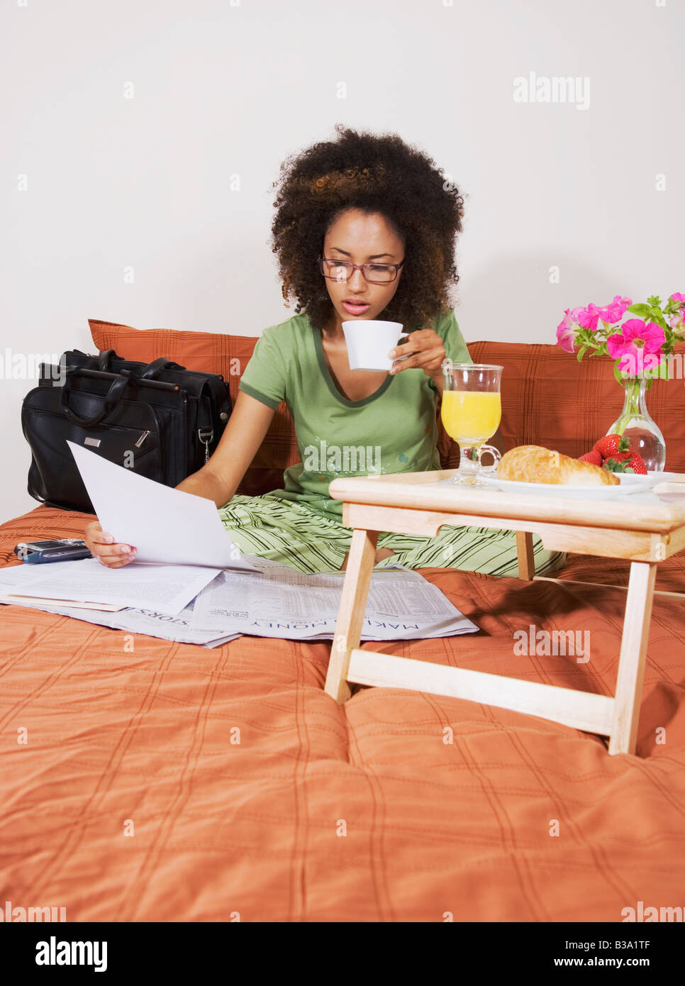 African woman eating breakfast in bed Stock Photo