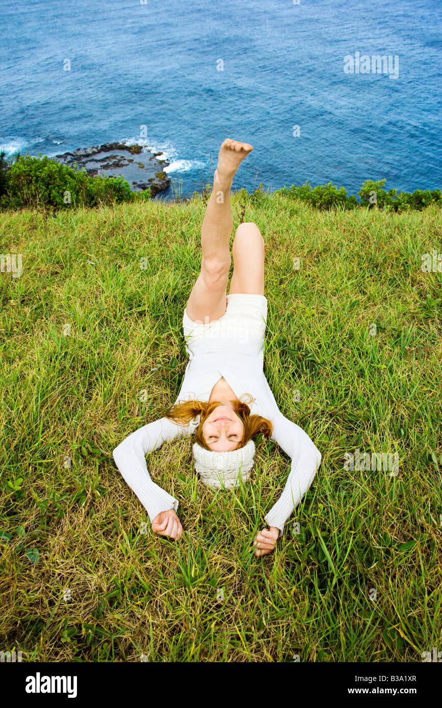 Joyful young woman relaxing in grass near ocean in Maui Hawaii - Stock Image