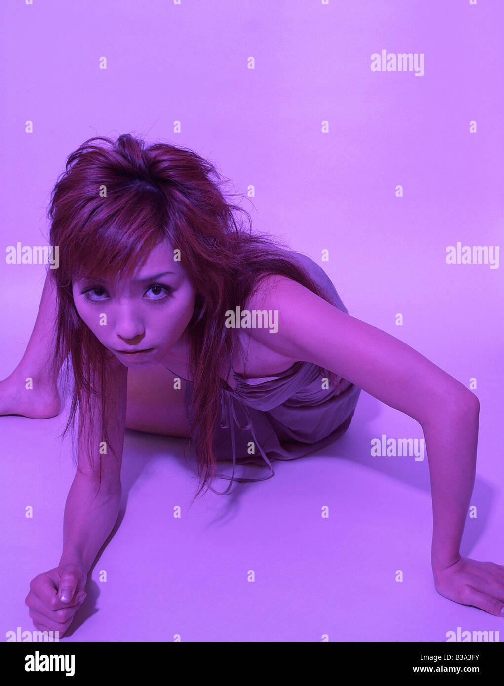 Woman in purple light lying in dramatic pose - Stock Image