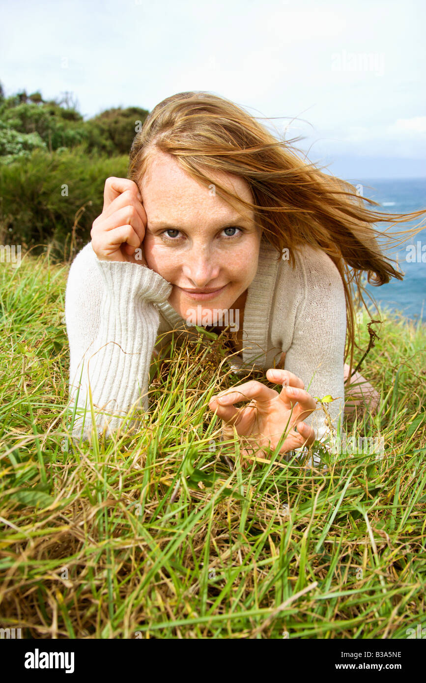 Portrait of young redheaded woman lying in grass looking at viewer with devilish grin - Stock Image
