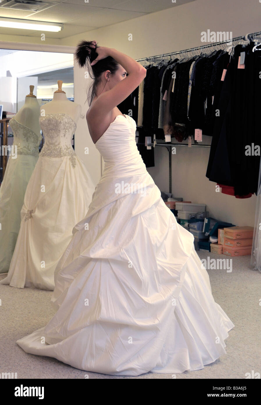 A 21 year old bride has a fitting of her bridal gown. She gathers up her hair to see how it looks. - Stock Image