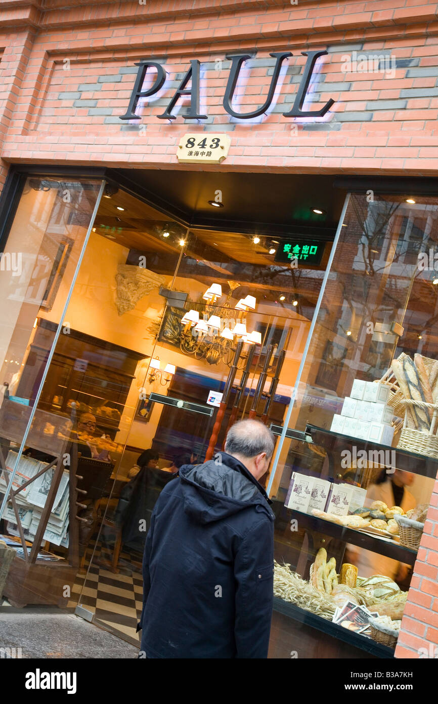 Chinese man looking into the window of French bakery Paul, in Shanghai - Stock Image