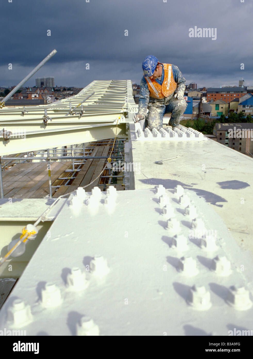 Man painting a bolted connection on a steel railway bridge, Newcastle upon Tyne, Tyne and Wear, England, UK. - Stock Image