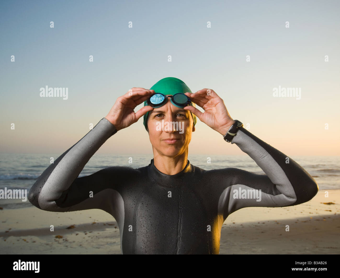 Hispanic woman wearing wetsuit and goggles Stock Photo