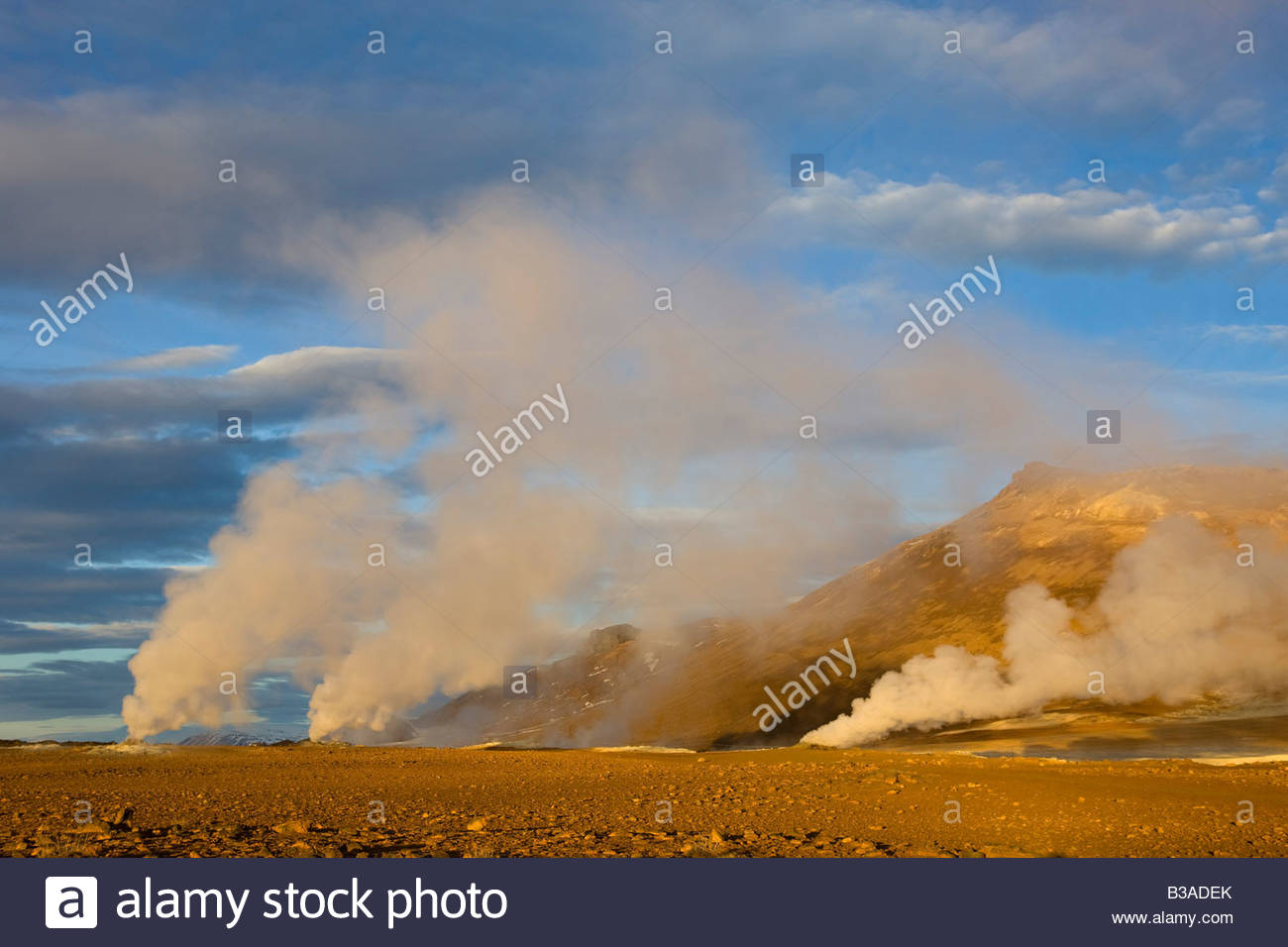 Several fumeroles shoot steam high into the sky at sunrise at Hverir, an especially active geothermal field in northern - Stock Image