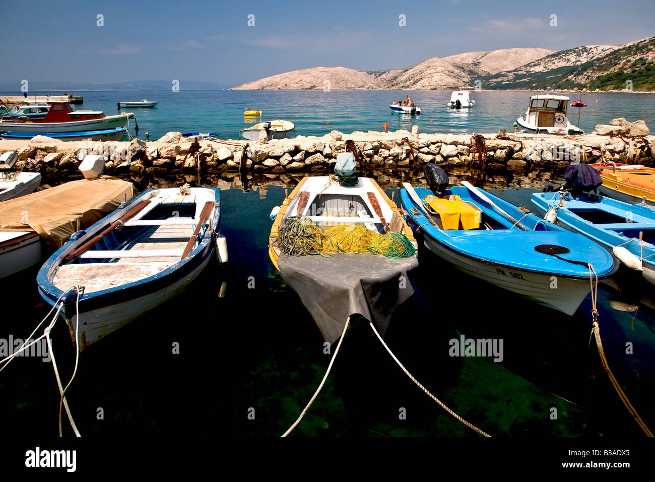 Fishing boats in Stara Baska harbour at the isle of Krk in Croatia - Stock Image