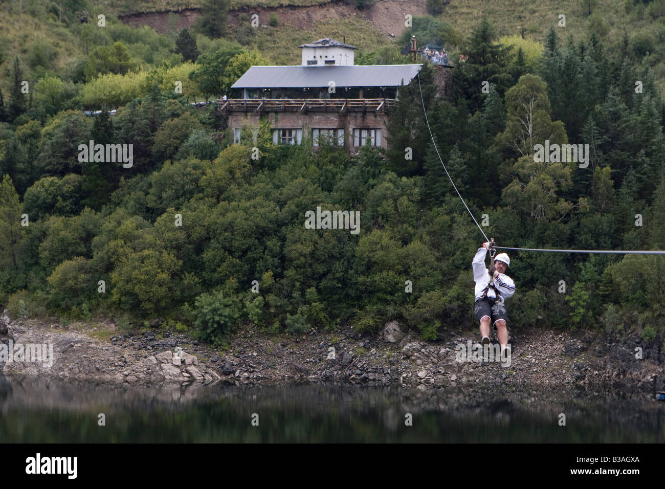 Tourist sliding down in a canopy cable in Dique Los Molinos dam Cordoba Argentina - Stock Image