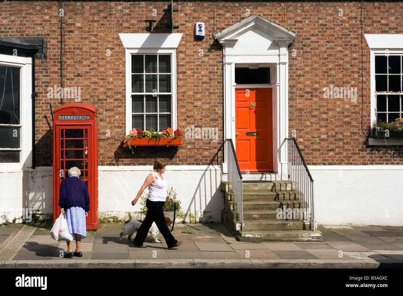 UK Cheshire Tarporley High Street K6 phone box outside former post office near red painted front door - Stock Image