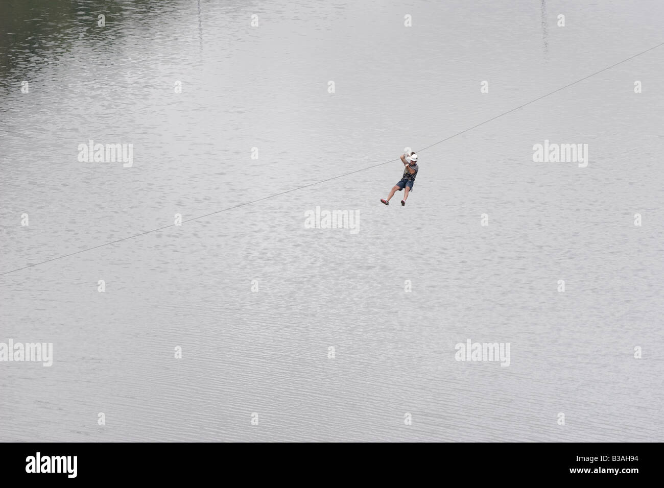 Tourist sliding down in a canopy cable across the Dique Los Molinos dam Cordoba Argentina - Stock Image