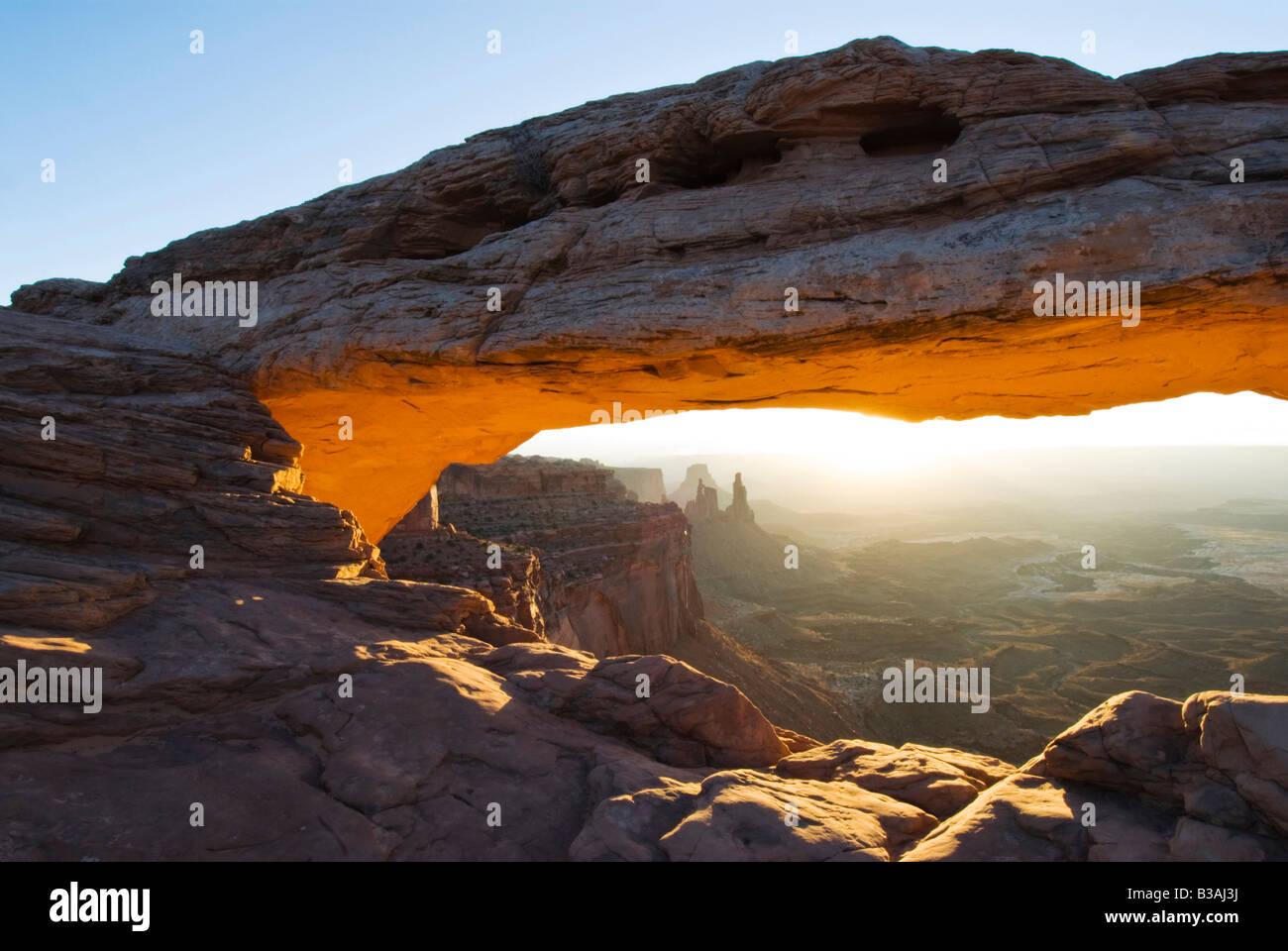 An orange glow illuminates Mesa Arch at sunrise Canyonlands National Park Utah - Stock Image