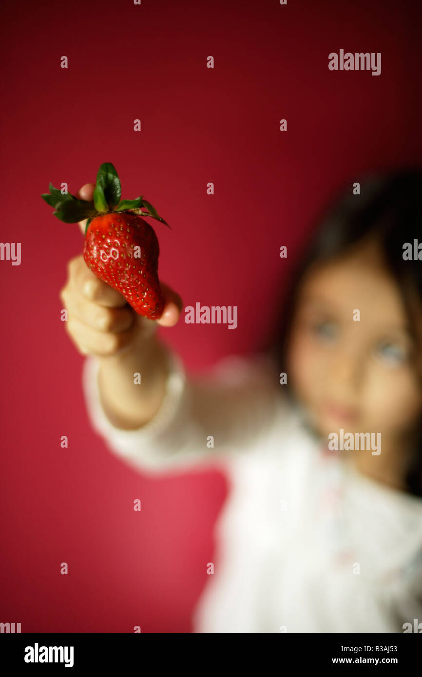 Five year old girl holds strawberry - Stock Image