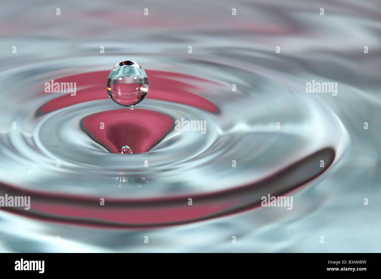 A water droplet bounces in the air after splashing into water and making ripples - Stock Image