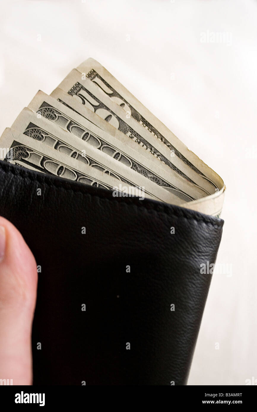 A hand holding a wallet full of cash isolated over a gold background - Stock Image