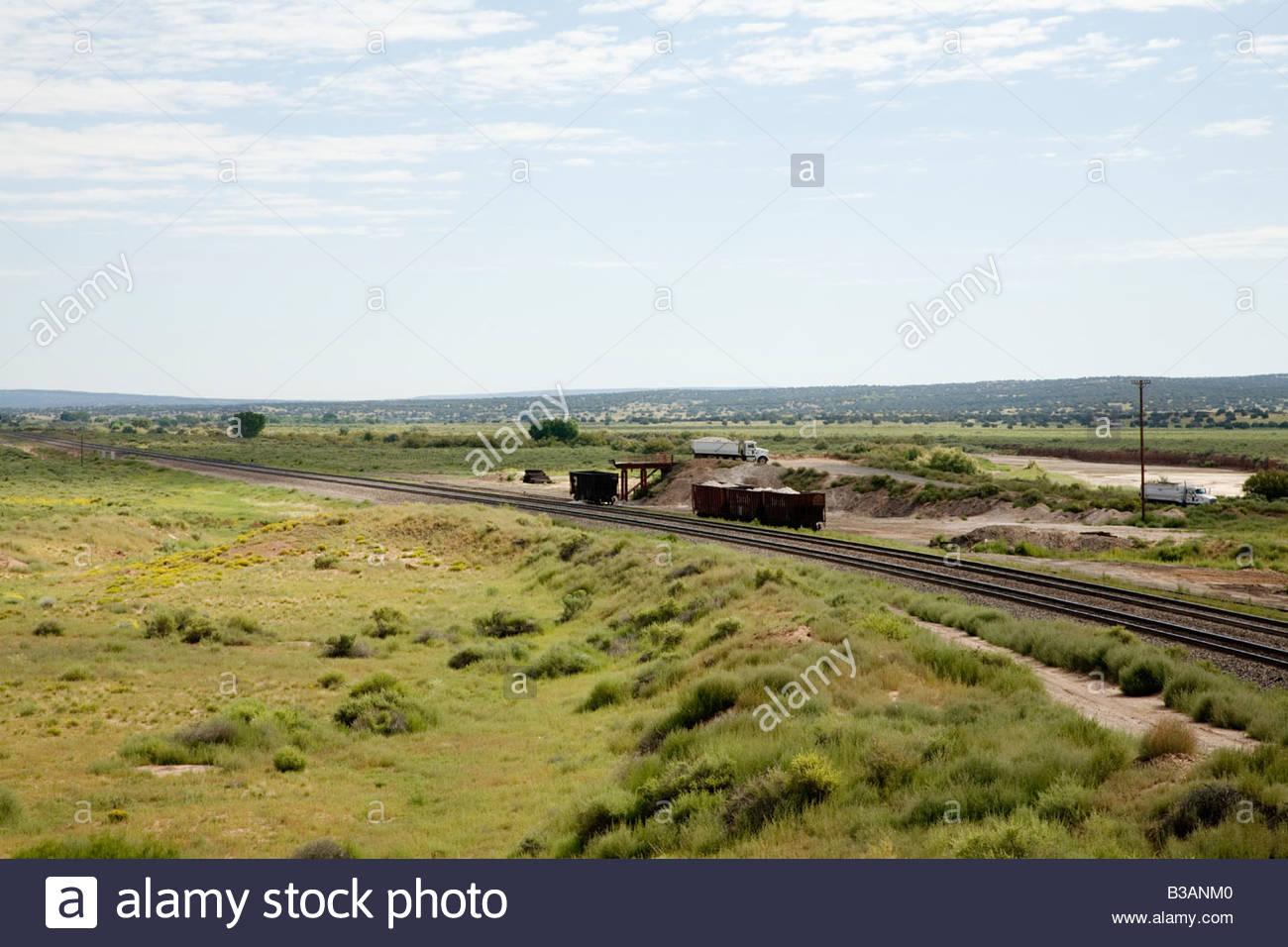 Truck dumping clay railcar dump dumptruck railroad loading car industrial minerals mining trucks - Stock Image