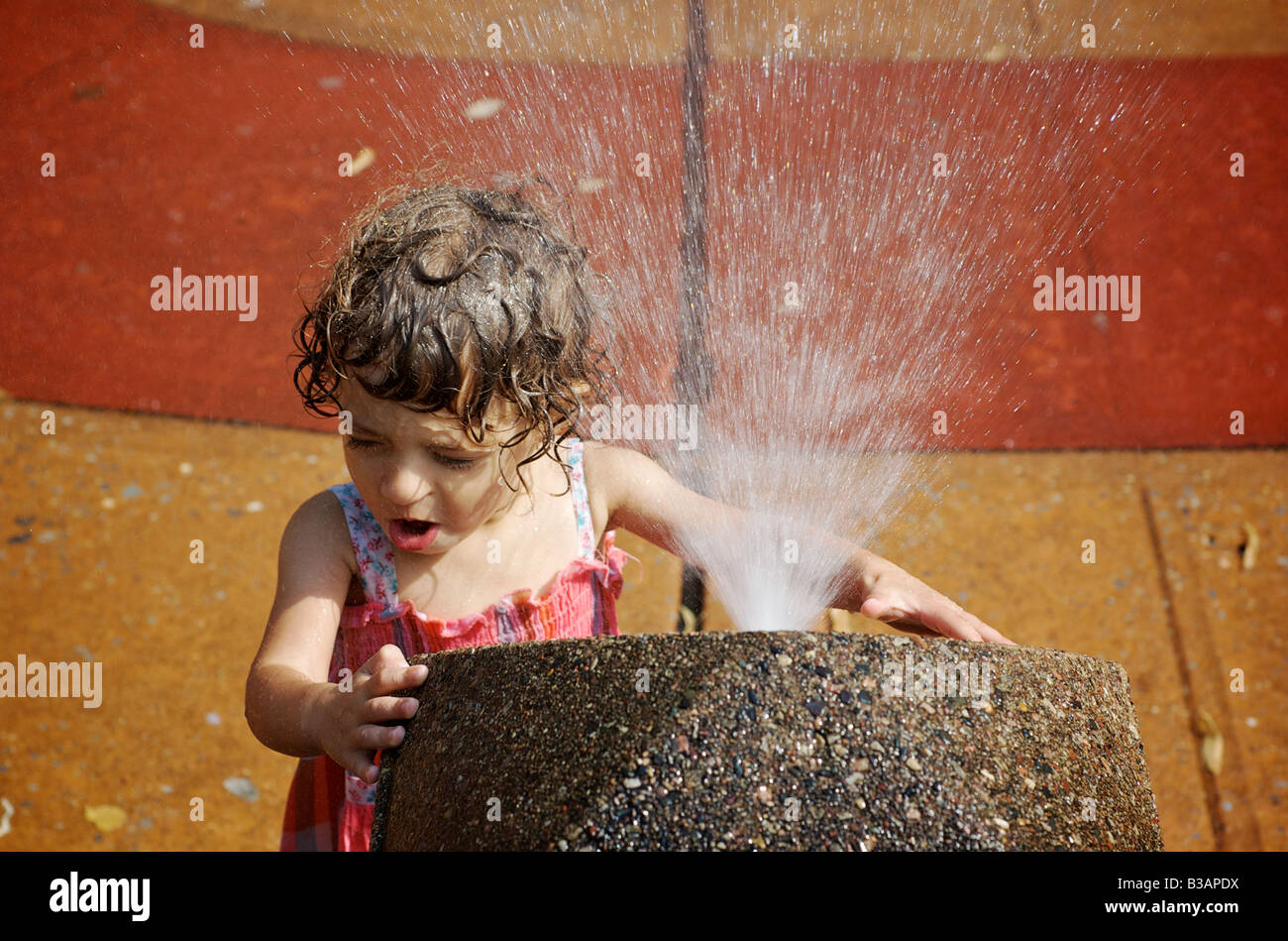Child sprayed by water fountain at urban playground in Brooklyn New York - Stock Image