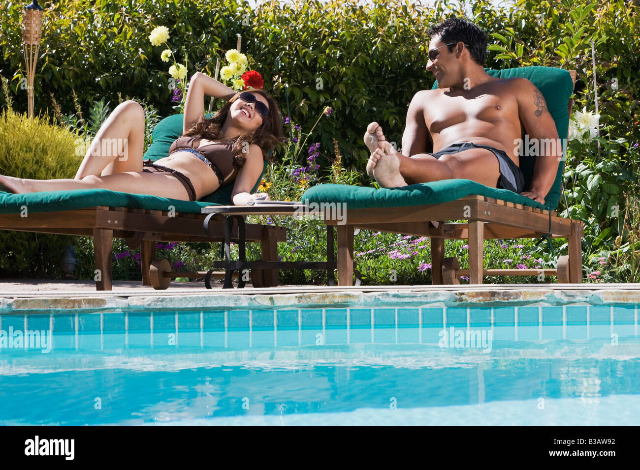 Multi-ethnic couple relaxing next to swimming pool Stock Photo