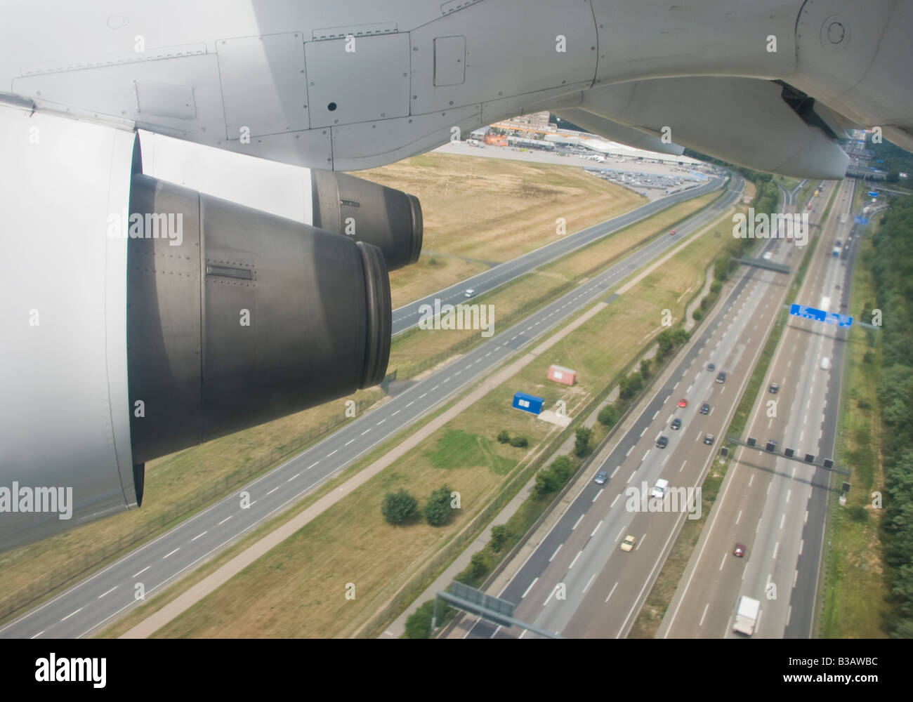 A plane flying over a motorway - Stock Image