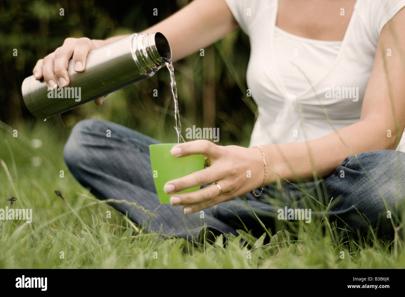 Woman pouring water from thermos in the park - Stock Image
