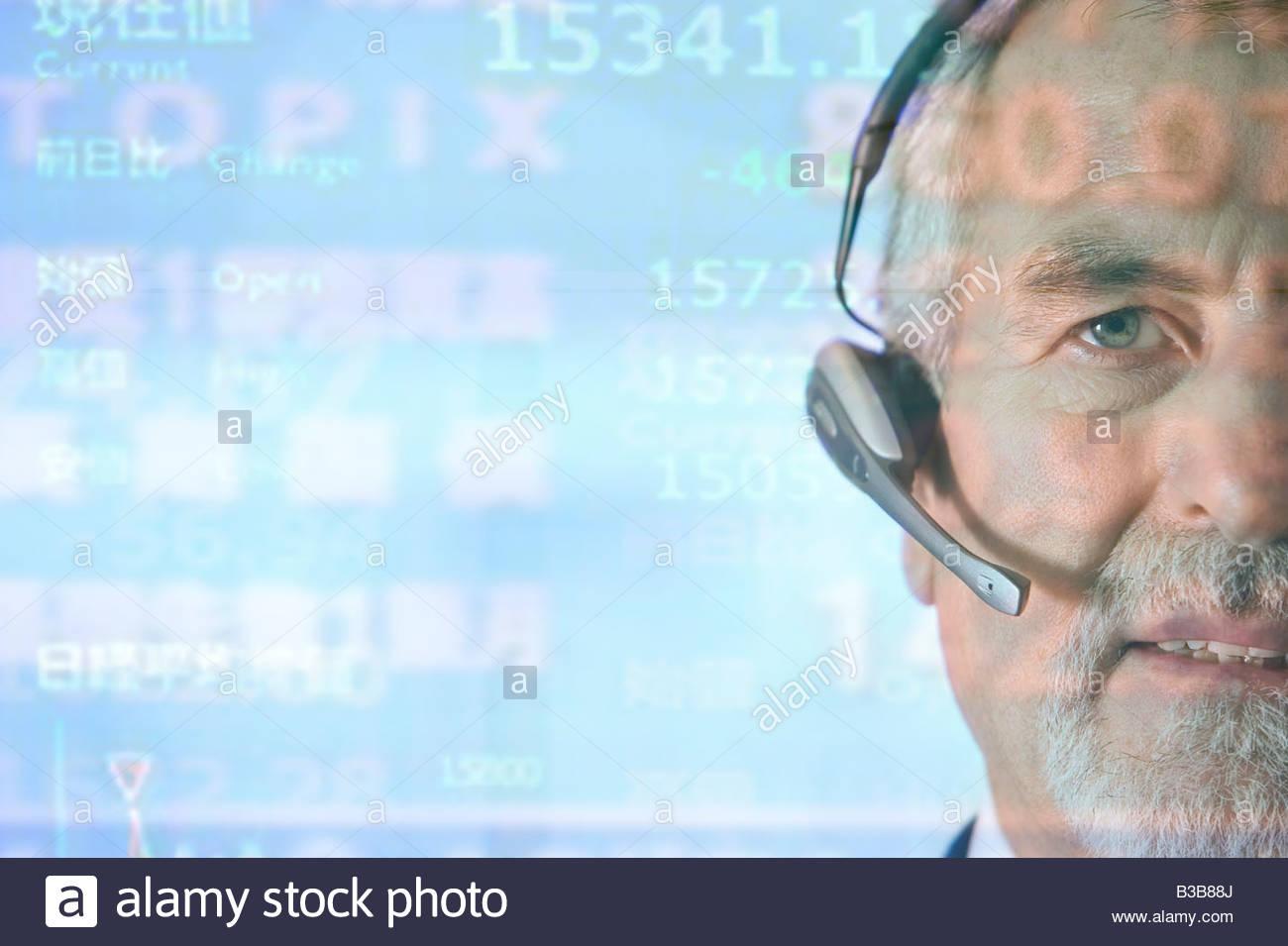 Businessman using telephone headset - Stock Image